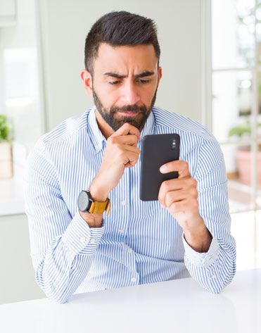 Confused man staring at his phone