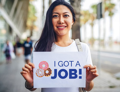 "Woman holding sign saying, ""I Got a Job!"""